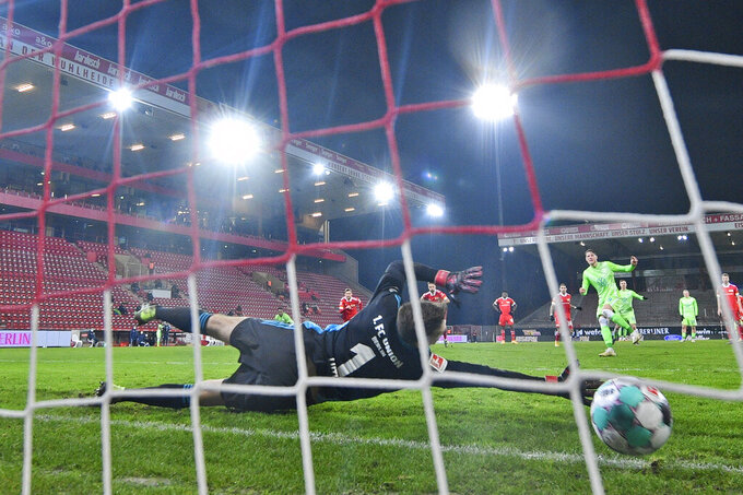 Wolfsburg's Wout Weghorst, background right, scores on a penalty shot past Union Berlin's goalkeeper Andreas Luthe during a German Bundesliga soccer match between Union Berlin and Wolfsburg, at the Stadion An der Alten Försterei, in Berlin, Saturday, Jan. 9, 2021.  (John Macdougall/Pool Photo via AP)
