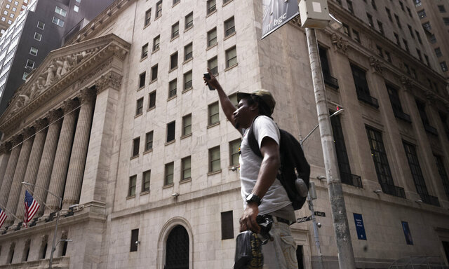 A man lifts his arm as he walks by the New York Stock Exchange, Thursday, July 30, 2020. Stocks are falling on Wall Street Thursday after reports showed that layoffs are continuing at a stubborn pace and that the U.S. economy contracted at a nearly 33% annual rate in the spring. (AP Photo/Mark Lennihan)