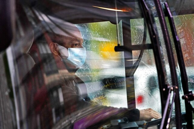 A Metro bus driver wears a mask to help prevent the spread of the coronavirus while while working on a rainy day, Tuesday, Oct. 13, 2020, in Portland, Maine. State health officials reported 26 new cases of COVID-19 on Tuesday, and no additional deaths. (AP Photo/Robert F. Bukaty)