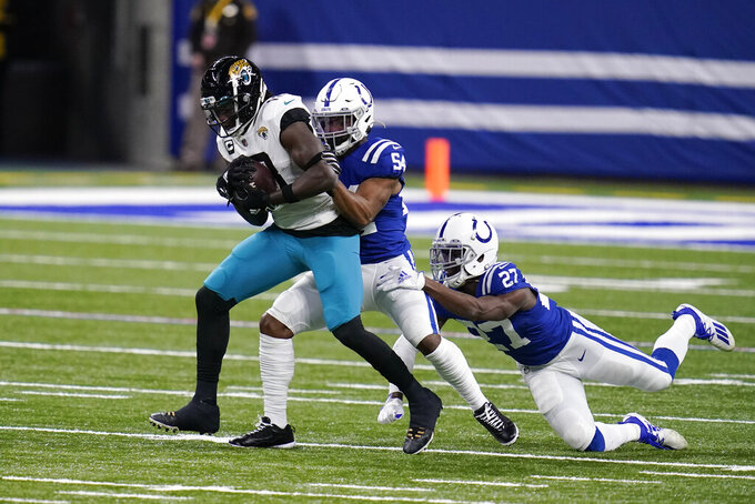 Jacksonville Jaguars' Chris Conley (18) is tackled by Indianapolis Colts' Anthony Walker (54) and Xavier Rhodes (27) during the first half of an NFL football game, Sunday, Jan. 3, 2021, in Indianapolis. (AP Photo/Michael Conroy)