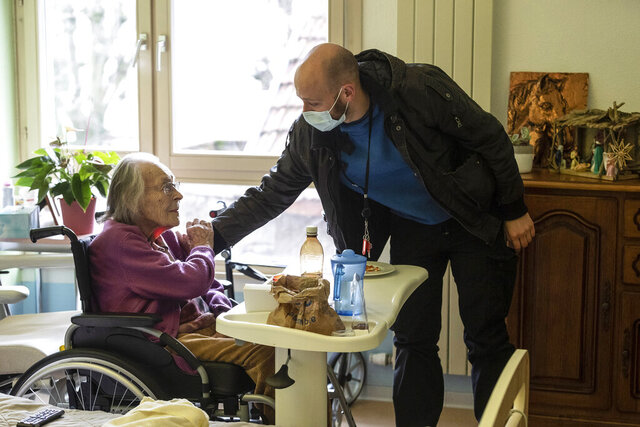 Marguerite Mouille, left, is greeted by her grandson Thierry Mouille at a nursing home in Kaysesberg, eastern France, Monday Dec. 21, 2020. Thierry Mouille is torturing himself over the government's Christmas offer of a three-week window of relaxed rules. He's changed his mind again and again about whether to bring his 94-year-old grandmother Marguerite out to share a holiday meal. (AP Photo/Jean-Francois Badias)