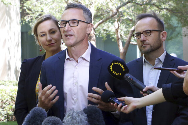 Australian Greens lawmakers, from left, Larissa Waters, Richard Di Natale and Adam Bandt speak to the media at Parliament House in Canberra, Australia, Monday, Feb. 3, 2020, after Di Natale resigned as the minor party's leader. Waters and Bandt had been Di Natale's co-deputy leaders and are among the favorites to replace him at a vote of Greens lawmakers on Tuesday. (AP Photo/Rod McGuirk)