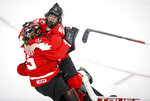 Canada goalie Ann-Renee Desbiens, left, and teammate Blayre Turnbull celebrate the team's overtime win against the United States in the IIHF hockey women's world championships title game in Calgary, Alberta, Tuesday, Aug. 31, 2021. (Jeff McIntosh/The Canadian Press via AP)