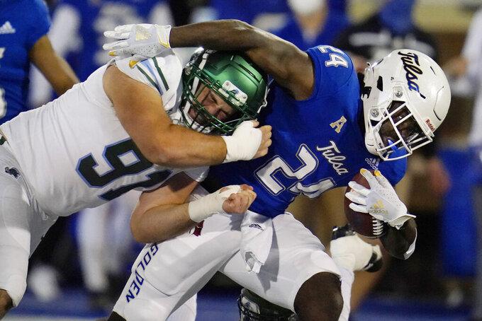 Tulane defensive end Noah Seiden (91) tackles Tulsa running back Corey Taylor II (24) during the first half of an NCAA college football game in Tulsa, Okla., Thursday, Nov. 19, 2020. (AP Photo/Sue Ogrocki)