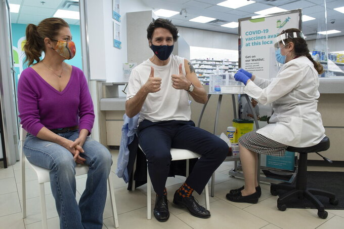 Sophie Gregoire Trudeau looks on as Prime Minister Justin Trudeau gives the thumbs up after being receiving his first COVID-19 AstraZeneca vaccination in Ottawa on Friday April 23, 2021.  (Adrian Wyld/The Canadian Press via AP)