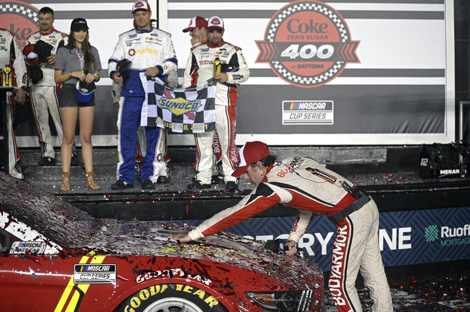 Ryan Blaney wipes confetti off the hood of his vehicle in Victory Lane after winning a NASCAR Cup Series auto race at Daytona International Speedway, Saturday, Aug. 28, 2021, in Daytona Beach, Fla. (AP Photo/Phelan M. Ebenhack)