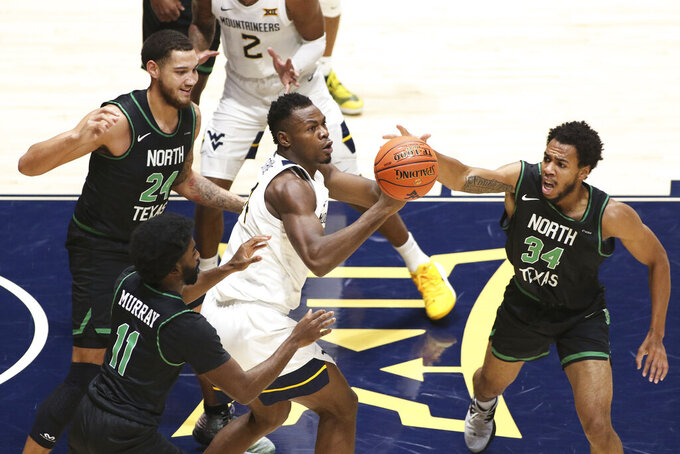 West Virginia forward Oscar Tshiebwe (34) passes while defended by North Texas forward Zachary Simmons (24), guard JJ Murray (11), and forward Terence Lewis II (34) during the first half of an NCAA college basketball game Friday, Dec. 11, 2020, in Morgantown, W.Va. (AP Photo/Kathleen Batten)