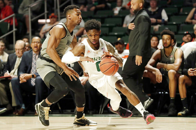 Miami guard Chris Lykes (0) drives past Wake Forest guard Andrien White during the first half of an NCAA college basketball game, Saturday, Feb. 15, 2020, in Coral Gables, Fla. (AP Photo/Wilfredo Lee)