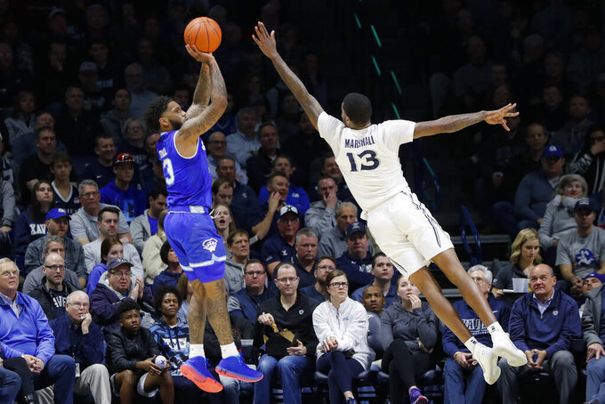 Seton Hall's Myles Powell, left, shoots against Xavier's Naji Marshall (13) during the first half of an NCAA college basketball game, Wednesday, Jan. 8, 2020, in Cincinnati. (AP Photo/John Minchillo)