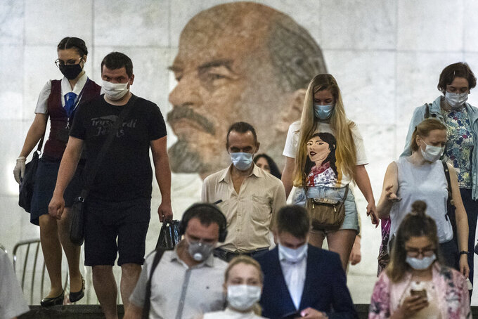 People wearing face masks to protect against coronavirus walk through the subway, with a portrait of Soviet founder Vladimir Lenin in the background, in Moscow, Russia, Wednesday, June 10, 2020. Moscow residents are no longer required to stay at home or obtain electronic passes for traveling around the city. All restrictions on taking walks, using public transportation or driving have been lifted as well. (AP Photo/Pavel Golovkin)