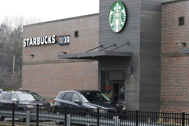 Customers wait for their order in their car at a Starbucks in Northbrook, Ill., Monday, March 16, 2020. Starbucks announced Sunday its company-owned stores across the U.S and Canada will shift to a