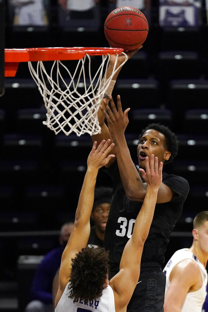 Michigan State forward Marcus Bingham Jr., top, shoots against Northwestern guard Ty Berry during the first half of an NCAA college basketball game in Evanston, Ill., Sunday, Dec. 20, 2020. (AP Photo/Nam Y. Huh)