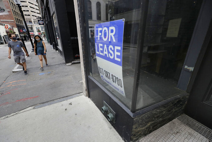 Passers-by wear masks out of concern for the coronavirus as they walk near the glass storefront, right, of an empty business location, in Boston's Downtown Crossing neighborhood, Sunday, Aug. 2, 2020. (AP Photo/Steven Senne)