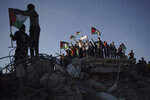 Protesters wave Palestinian flags as they stand atop the rubble of a building destroyed by an Israeli airstrike last month, during a protest against a march by Jewish ultranationalists through east Jerusalem, in Beit Lahia, northern Gaza Strip, Tuesday, June 15, 2021. (AP Photo/Felipe Dana)