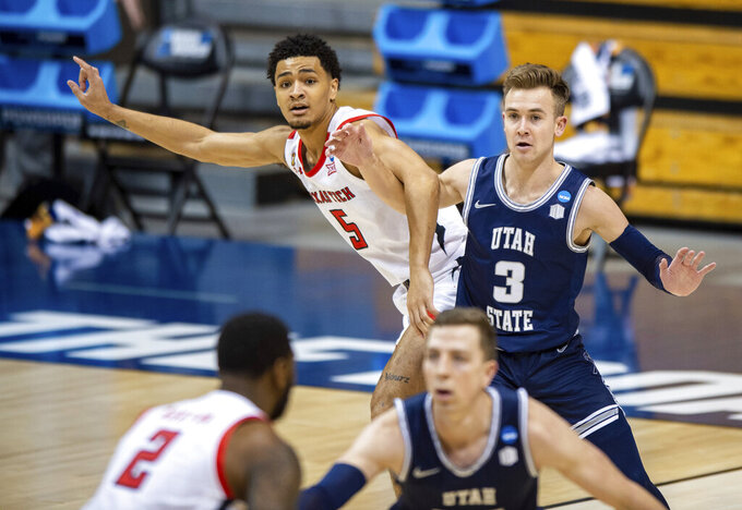 Texas Tech guard Micah Peavy (5) and Utah State guard Steven Ashworth (3) battle for position under the basket during the first half of a first round game in the NCAA men's college basketball tournament, Friday, March 19, 2021, in Bloomington, Ind. (AP Photo/Doug McSchooler)