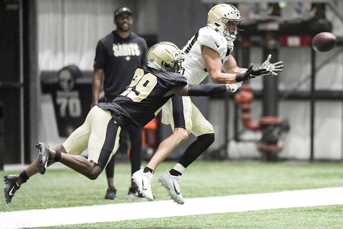 New Orleans Saints wide receiver Chris Hogan (80) catches the ball under pressure from cornerback Paulson Adebo (29) during NFL football practice, Thursday, Aug. 12, 2021, in Metairie, La. (Max Becherer/The Times-Picayune/The New Orleans Advocate via AP)