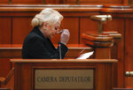Romanian Prime Minister Viorica Dancila removes her glasses after her speech ahead of a no confidence vote in Bucharest, Romania, Thursday, Oct. 10, 2019. Romania's government is facing a no confidence vote called by opposition parties. (AP Photo/Vadim Ghirda)