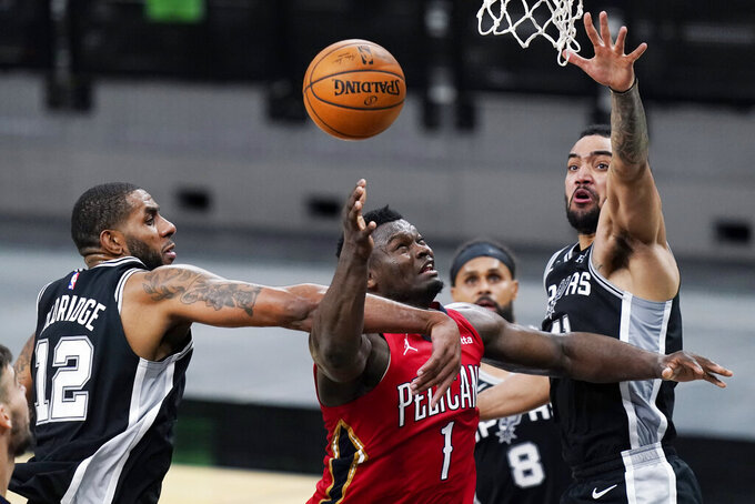 New Orleans Pelicans forward Zion Williamson (1) is fouled by San Antonio Spurs center LaMarcus Aldridge (12) as he tires to score during the second half of an NBA basketball game in San Antonio, Saturday, Feb. 27, 2021. (AP Photo/Eric Gay)