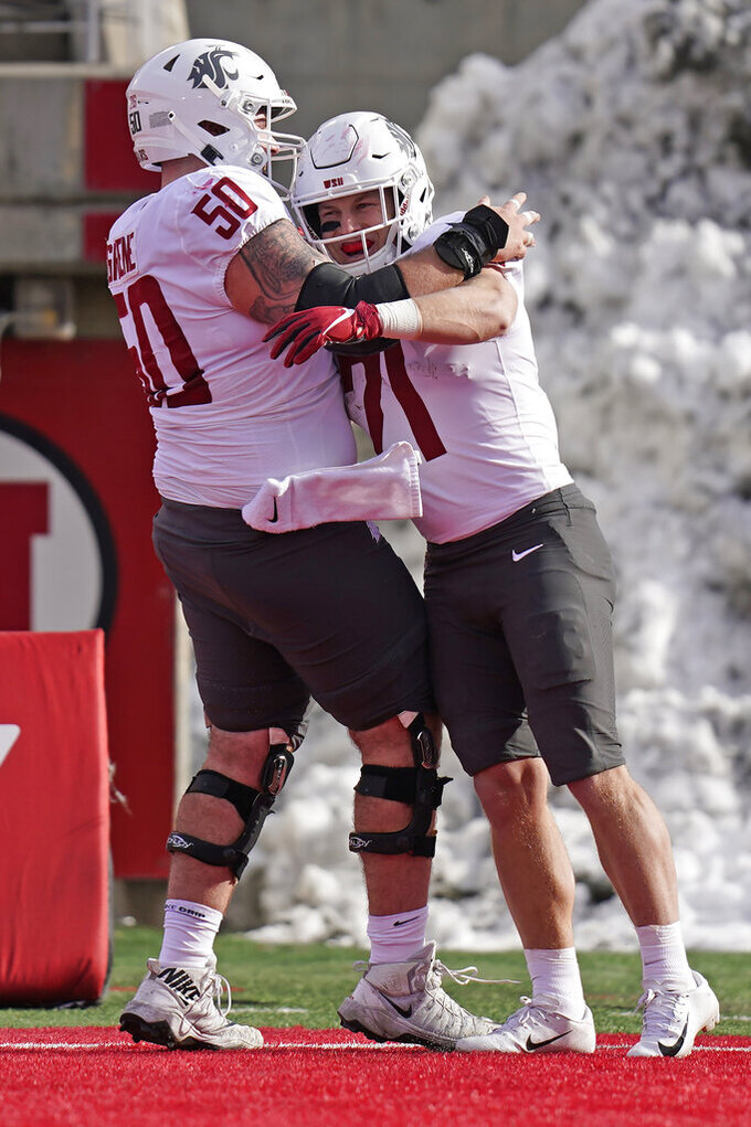 Washington State running back Max Borghi (21) celebrates with teammate Brian Greene (50) after scoring against Utah during the first half of an NCAA college football game Saturday, Dec. 19, 2020, in Salt Lake City. (AP Photo/Rick Bowmer)