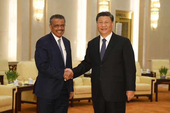 "FILE - In this Jan. 28, 2020, file photo, Tedros Adhanom Ghebreyesus, director general of the World Health Organization, left, shakes hands with Chinese President Xi Jinping before a meeting at the Great Hall of the People in Beijing. Throughout January, the World Health Organization publicly praised China for what it called a speedy response to the new coronavirus. It repeatedly thanked the Chinese government for sharing the genetic map of the virus ""immediately"" and said its work and commitment to transparency were ""very impressive, and beyond words."" But behind the scenes, there were significant delays by China and considerable frustration among WHO officials over the lack of outbreak data, The Associated Press has found. (Naohiko Hatta/Pool Photo via AP, File)"