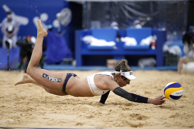 April Ross, of the United States, dives for the ball during a women's beach volleyball match against the Netherlands at the 2020 Summer Olympics, Friday, July 30, 2021, in Tokyo, Japan. (AP Photo/Felipe Dana)