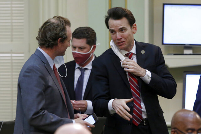 In this photo taken Monday, June 15, 2020, Republican Assemblymen James Gallagher, of Yuba City, left, and Kevin Kiley, of Rocklin confer at the Capitol in Sacramento, Calif. An appellate judge, on Wednesday, June 17, stayed a lower court's order barring  California Gov. Gavin Newsom from issuing directives that might conflict with state law. Gallagher and Kiley sued Newsom saying he had exceeded his authority.(AP Photo/Rich Pedroncelli)