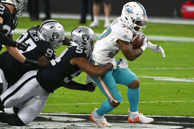 Las Vegas Raiders middle linebacker Raekwon McMillan (54) tackles Miami Dolphins running back Myles Gaskin (37) during the first half of an NFL football game, Saturday, Dec. 26, 2020, in Las Vegas. (AP Photo/David Becker)