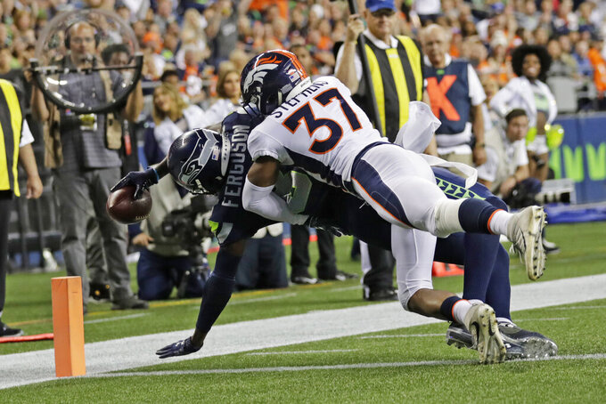 Seattle Seahawks wide receiver Jazz Ferguson stays in bounds for a touchdown after catching a pass under pressure from Denver Broncos cornerback Linden Stephens (37) during the second half of an NFL football preseason game Thursday, Aug. 8, 2019, in Seattle. (AP Photo/Stephen Brashear)