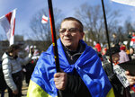 Covered by Ukrainian state flag a man takes part in celebration in Minsk, Belarus, Sunday, March 24, 2019, on the eve of March 25, a traditional day of demonstration for the opposition.  Many people gather to mark what they call Freedom Day, on the 101st anniversary of the 1918 declaration of the first, short-lived independent Belarus state, the Belarusian People's Republic lasted until 1919. (AP Photo/Sergei Grits)