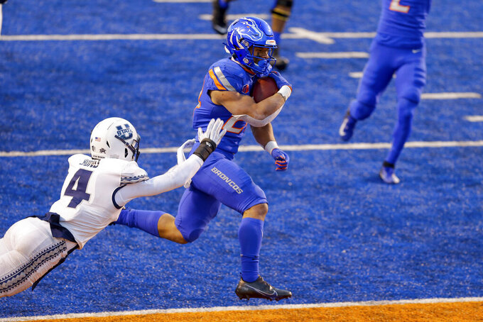 Boise State wide receiver Khalil Shakir (2) avoids Utah State safety Shaq Bond (4) for a touchdown in the first half of an NCAA college football game Saturday, Oct. 24, 2020, in Boise, Idaho. (AP Photo/Steve Conner)