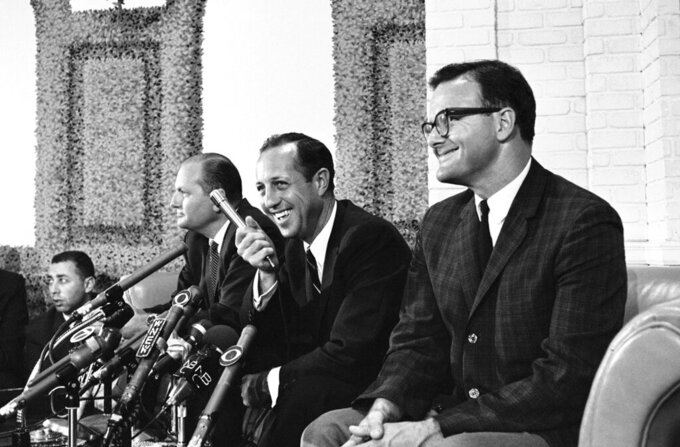 FILE - In this June 9, 1966, file photo, Pete Rozelle grins as he answers questions about a merger agreement between the National and American Football leagues in New York. At left is Tex Schramm, NFL President and head of the Dallas Cowboys. At right is Lamar Hunt, president of the Kansas City Chiefs. (AP Photo/John Duricka, File)