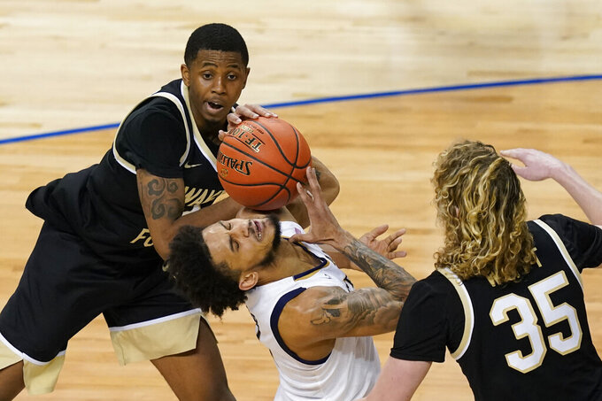 Notre Dame guard Prentiss Hubb, center, grabs a rebound as Wake Forest guard Ian DuBose, left, and teammate guard Carter Whitt (35) defend during the second half of an NCAA college basketball game in the first round of the Atlantic Coast Conference tournament in Greensboro, N.C., Tuesday, March 9, 2021. (AP Photo/Gerry Broome)