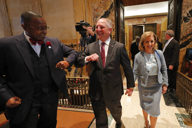 Louisiana Gov. John Bel Edwards, center, bumps elbows with state Rep. Patrick Jefferson, D-Homer, instead of his traditional handshake, as a precaution against the COVID-9 Coronavirus, as he walks down the aisle of the House Chambers for the opening of the 2020 general legislative session in Baton Rouge, La., Monday, March 9, 2020. Edwards subsequently announced to the legislature that Louisiana today had its first confirmed case of the virus in Jefferson Parish. Right is Edwards wife Donna Edwards. (AP Photo/Gerald Herbert)
