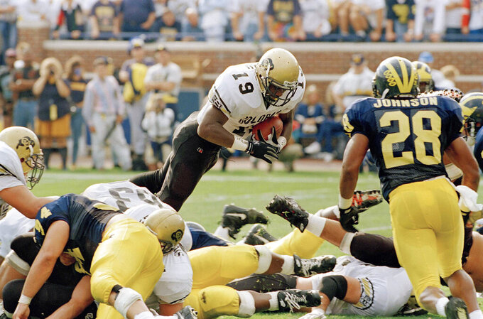 FILE - In this Sept. 24, 1994, file photo, Colorado's Rashaan Salaam (19) dives over the goal line for a 1-yard touchdown against Michigan in the first quarter of an NCAA college football game, in Ann Arbor, Mich. A glance at the list of candidates eligible for selection to the College Football Hall of Fame is likely to produce the following reaction: How is that guy not in yet? Heisman Trophy winners Salaam, Carson Palmer and Eric Crouch are still waiting. (AP Photo/Werner Slocum, File)