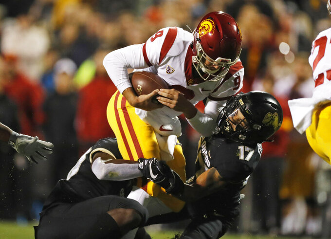 Southern California quarterback Kedon Slovis is sacked by Colorado linebacker Davion Taylor, left, and cornerback K.J. Trujillo during the first half of an NCAA college football game Friday, Oct. 25, 2019, in Boulder, Colo. (AP Photo/David Zalubowski)