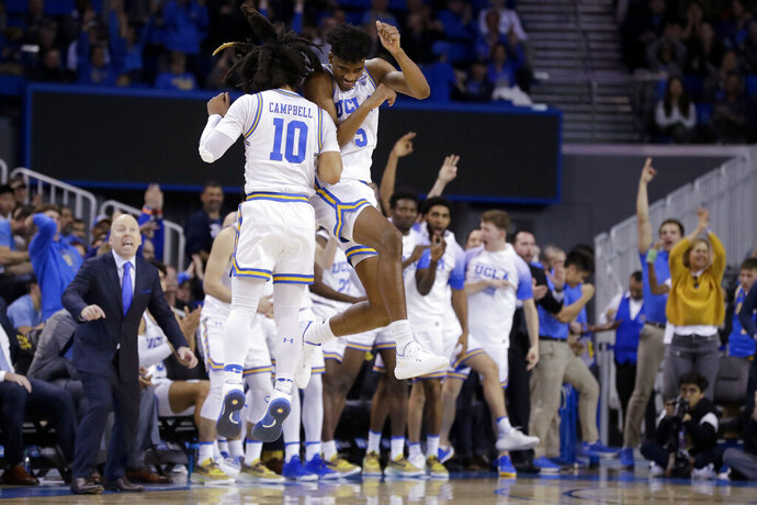 UCLA guard Chris Smith (5) celebrates with guard Tyger Campbell after scoring during the second half of the team's NCAA college basketball game against Washington in Los Angeles, Saturday, Feb. 15, 2020. (AP Photo/Chris Carlson)