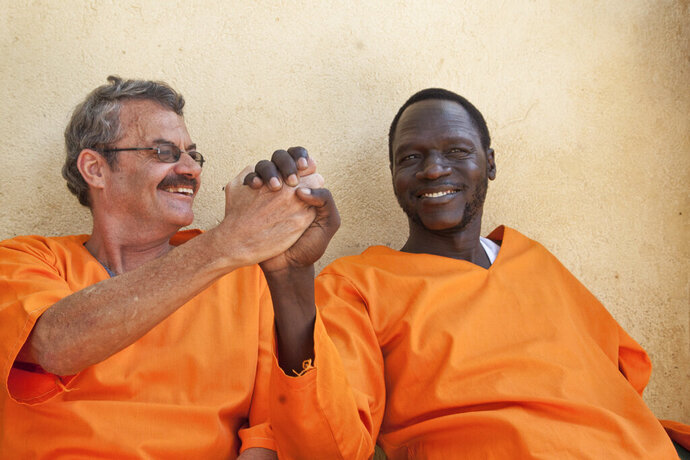 In this photo taken Friday, Nov. 2, 2018, James Gatdet Dak, right, the longtime spokesman of opposition leader Riek Machar, clasps hands with William Endley, left, a South African former defense colonel who also worked with the opposition, as they prepare to be released from prison after their death sentence was pardoned, in Juba, South Sudan. Dak, one of the highest-profile detainees during South Sudan's five-year civil war, has shared his account with The Associated Press, after his release under a fragile peace deal signed in September. (AP Photo)
