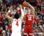 Wisconsin guard Trevor Anderson, right, goes up to shoot in front of Ohio State guard Duane Washington during the first half of an NCAA college basketball game in Columbus, Ohio, Friday, Jan. 3, 2020. (AP Photo/Paul Vernon)