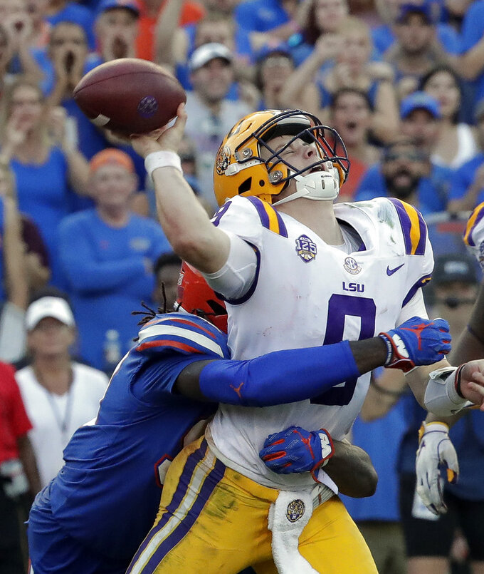 Florida defensive lineman Jachai Polite, left, hits LSU quarterback Joe Burrow just as he releases a pass during the second half of an NCAA college football game Saturday, Oct. 6, 2018, in Gainesville, Fla. (AP Photo/John Raoux)