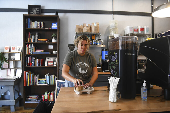 Teen worker Courtney Collins, 19, gets a customers order together at Harvest Moon Coffee & Chocolates in Tarentum, Pa. on Friday, July 16, 2021. (Kristina Serafini/Pittsburgh Tribune-Review via AP)