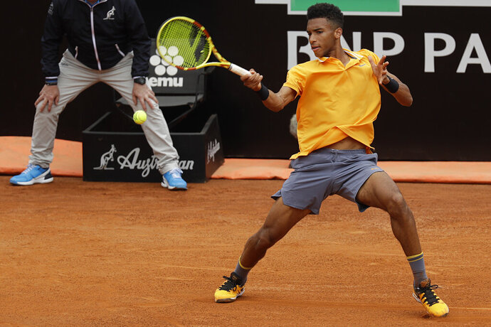 FILE - In this Monday, May, 13, 2019 filer, Canada's Felix Auger-Aliassime returns the ball to Croatia's Borna Coric during their match at the Italian Open tennis tournament, in Rome. It's typically Canadian that Denis Shapovalov, Felix Auger-Aliassime and Bianca Andreescu are each children of immigrants. What's not typical is that they have all simultaneously broken into the world's elite ranks of tennis players _ and will all be worth watching when the French Open begins Sunday. (AP Photo/Gregorio Borgia, File)