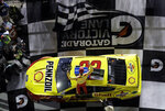 Joey Logano (22) climbs onto his car as he celebrates his win in the second NASCAR Daytona 500 qualifying auto race Thursday, Feb. 14, 2019, at Daytona International Speedway in Daytona Beach, Fla. (AP Photo/Chris O'Meara)
