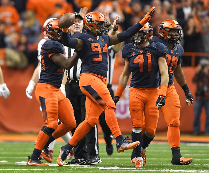 Syracuse defensive lineman Alton Robinson (94) celebrates a defensive fumble recovery during the first half of an NCAA college football game against Louisville in Syracuse, N.Y., Friday, Nov. 9, 2018. (AP Photo/Adrian Kraus)