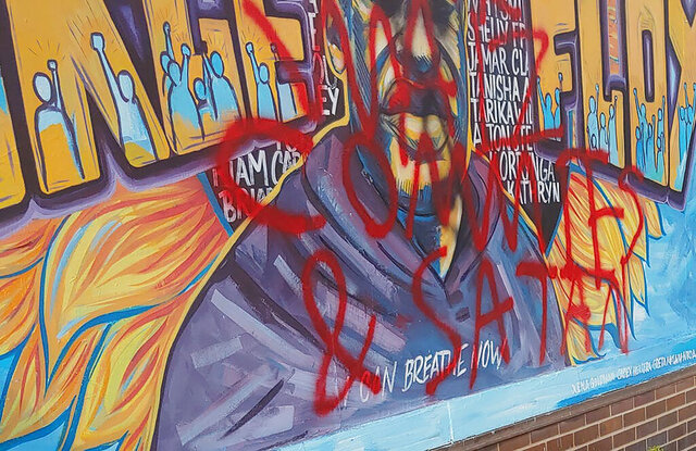 A mural dedicated to George Floyd, a Black man who died in May after a white police officer pressed a knee to his neck in Minneapolis, is seen vandalized with red paint on Tuesday, Oct. 6, 2020, in Minneapolis. It's the second time that the mural has been damaged. (Matt McKinney/Star Tribune via AP)