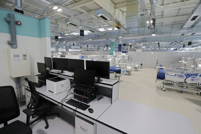 A desk with computer screens and new beds sit in the empty Isabel Zendal new hospital during the official opening in Madrid, Spain, Tuesday, Dec. 1, 2020. Authorities in Madrid are holding a ceremony to open part of a 1,000-bed hospital for emergencies that critics say is no more than a vanity project, a building with beds not ready to receive patients and unnecessary now that contagion and hospitalizations are waning. Spain has officially logged 1.6 million infections and over 45,000 deaths confirmed for COVID-19 since the beginning of the year. (AP Photo/Paul White)