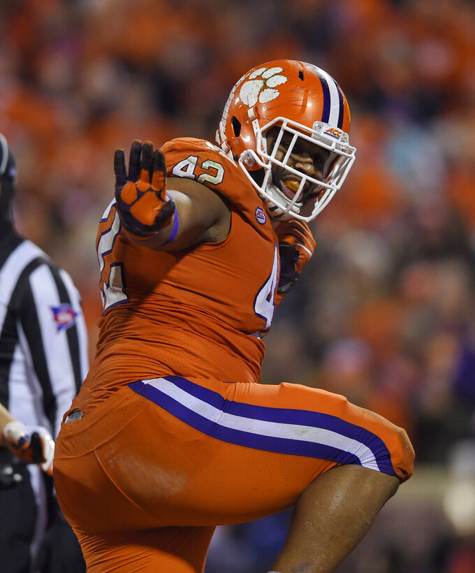 FILE - In this Nov. 24, 2018, file photo, Clemson tackle Christian Wilkins does the Heisman pose after scoring a touchdown during the first half of a game against South Carolina, in Clemson, S.C. Wilkins was named to the 2018 AP All-America NCAA college football team, Monday, Dec. 10, 2018.(AP Photo/Richard Shiro, File)