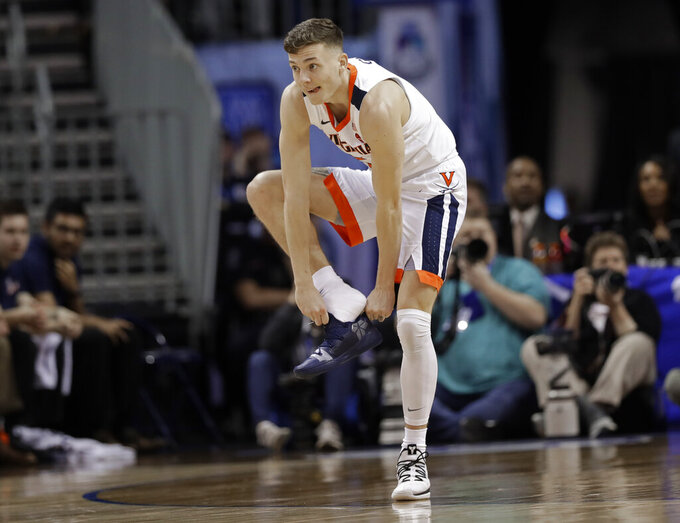 Virginia's Kyle Guy (5) puts on his shoe after losing it during the first half of an NCAA college basketball game against North Carolina State in the Atlantic Coast Conference tournament in Charlotte, N.C., Thursday, March 14, 2019. (AP Photo/Chuck Burton)