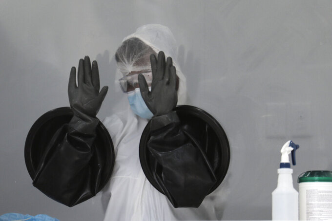 A health care worker air dries her gloves after sanitizing her equipment while working at a walk-up COVID-19 testing site during the coronavirus pandemic, Friday, July 17, 2020, in Miami Beach, Fla. The mobile testing truck is operated by Aardvark Mobile Health, which has partnered with the Florida Division of Emergency Management. People getting tested are separated from nurses via a glass pane. (AP Photo/Lynne Sladky)