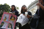 Women hold posters with photographs of victims during a tribute for murdered women, in the Alameda park of Mexico City, Saturday, Aug. 24, 2019. A small group of women constructed a memorial made of hand-knit hearts. The knit-in on came on the heels of rowdy protests sparked by outrage over bungled investigations into alleged rapes of teenagers by local policemen. (AP Photo/Ginnette Riquelme)