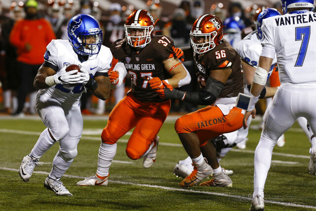 Buffalo running back Jaret Patterson, left, carries the ball while Bowling Green linebacker Darren Anders (37) and defensive lineman Ja'von Lyons (56) close in during the first half of an NCAA college football game in Bowling Green, Ohio, Tuesday, Nov. 17, 2020. (Scott W. Grau/Sentinel-Tribune via AP)